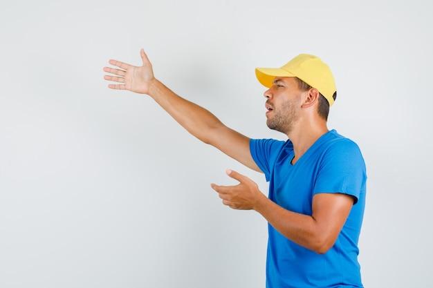 青いtシャツで誰かを呼ぶ配達人 無料写真
