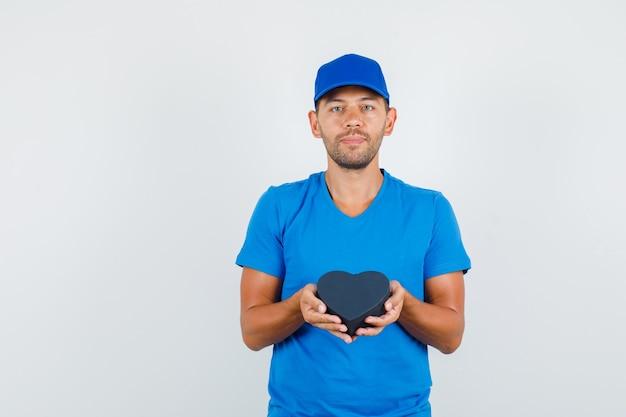青いtシャツで黒いプレゼントボックスを保持している配達人 無料写真