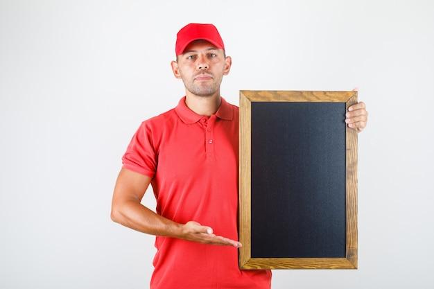 Доставка человек, держащий доску в красной форме, вид спереди. Бесплатные Фотографии