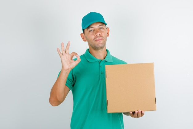 Delivery man holding box and doing ok sign in green t-shirt and cap Free Photo