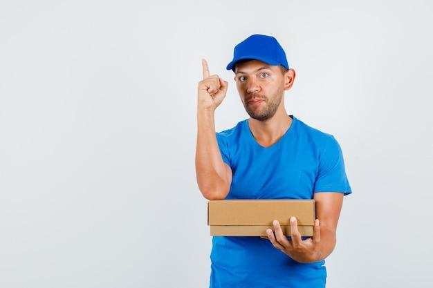 青いtシャツで指を上に段ボール箱を保持している配達人 無料写真