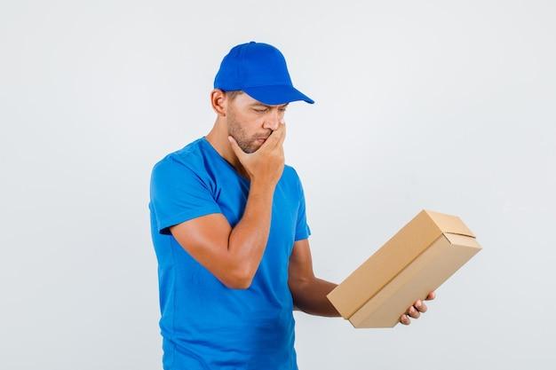 青いtシャツの口に手で段ボール箱を保持している配達人 無料写真