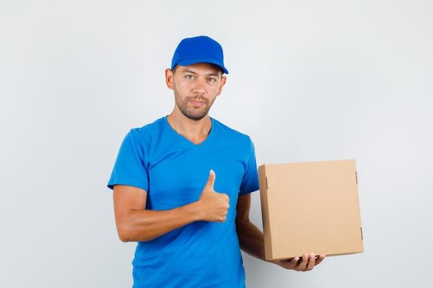 青いtシャツの親指で段ボール箱を保持している配達人 無料写真