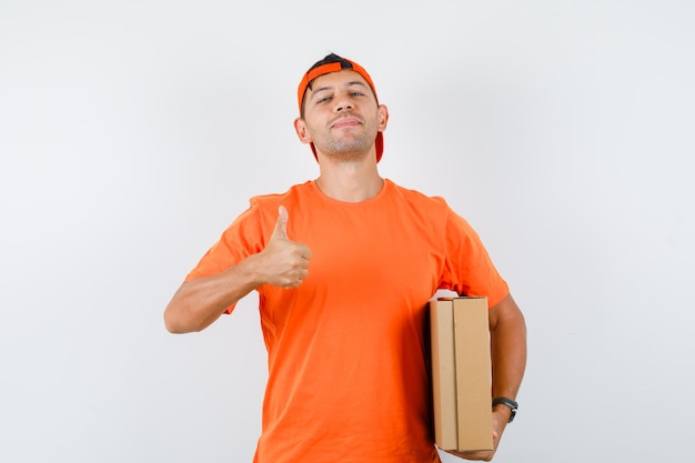 Delivery man holding cardboard box with thumb up in orange t-shirt and cap and looking confident Free Photo