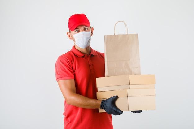 Uomo di consegna che tiene scatole di cartone e sacchetto di carta in uniforme rossa, mascherina medica, vista frontale dei guanti. Foto Gratuite