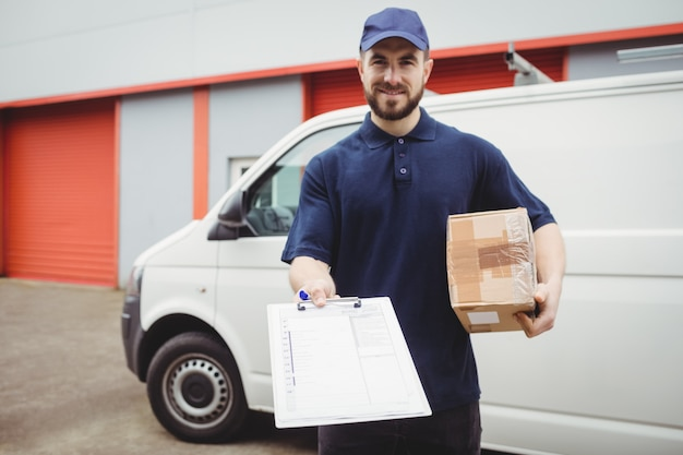 Delivery man holding clipboard and package in front of his van Premium Photo