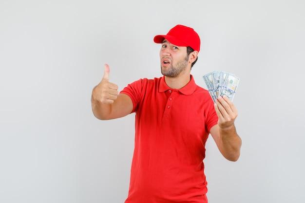 赤いtシャツに親指を立ててドル紙幣を保持している配達人 無料写真