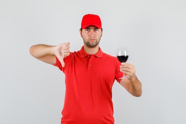 赤いtシャツで親指を下にアルコールのガラスを保持している配達人 無料写真