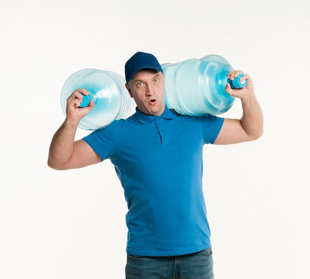 Delivery man holding heavy water bottles on shoulders Free Photo