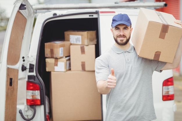 Delivery man holding package in front of his van Premium Photo