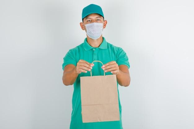Доставщик, держащий бумажный пакет в зеленой футболке с кепкой и маской Бесплатные Фотографии