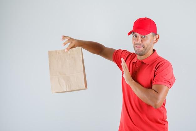 Доставщик держит бумажный пакет в красной форме и выглядит защитным Бесплатные Фотографии