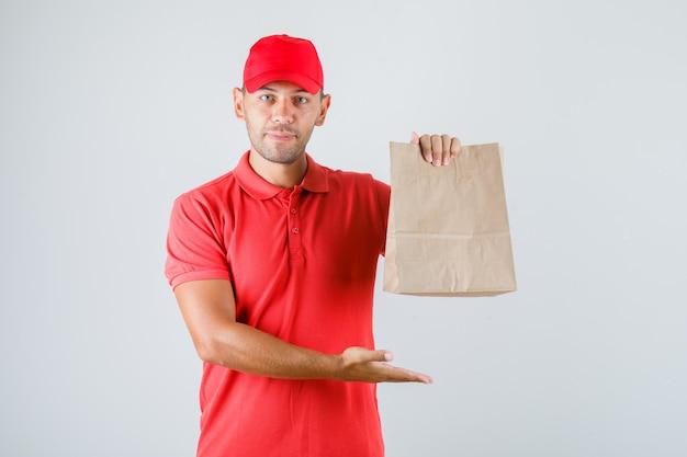 Доставщик, держащий бумажный пакет в красной форме Бесплатные Фотографии
