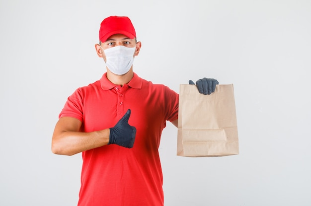 Delivery man holding paper bag and showing thumb up in red uniform Free Photo