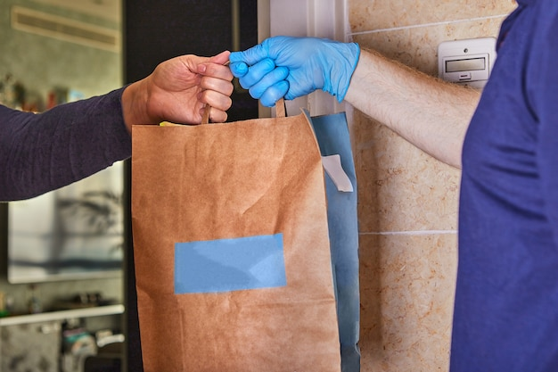 Delivery man holding paper bags in medical rubber gloves. quarantine. coronavirus. copy space. fast and free transport delivery. online store and express delivery. Premium Photo