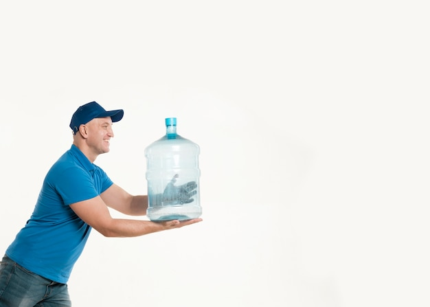 Delivery man holding water bottle and posing Free Photo