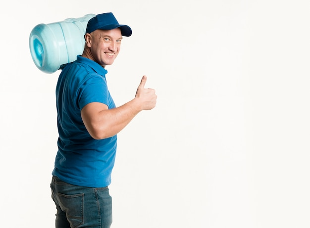Delivery man holding water bottle and showing thumbs up Free Photo