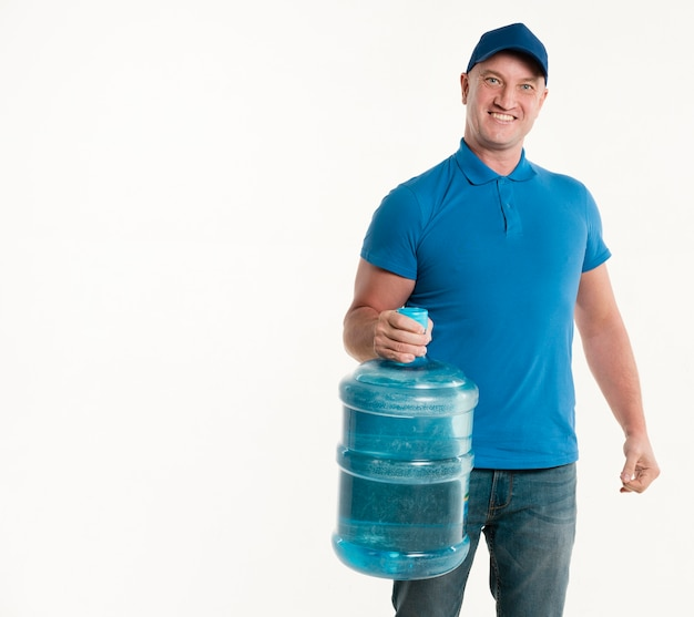 Delivery man holding water bottle and smiling Free Photo