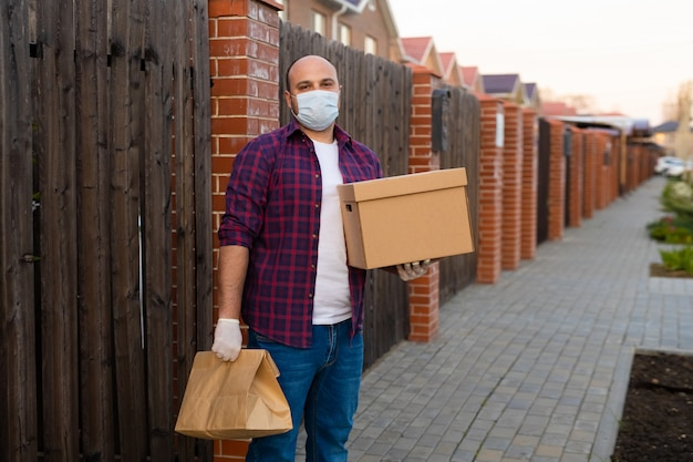 Delivery man holds a cardboard box and wear a face mask for coronavirus prevention Premium Photo