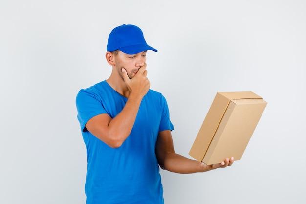 Курьер в синей футболке, кепке держит картонную коробку рукой во рту и задумчиво смотрит Бесплатные Фотографии
