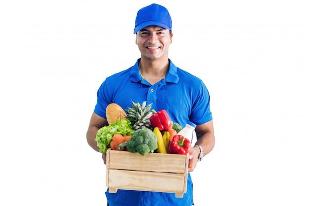 Доставка человек в синей форме, перевозящих пакет продуктов питания с овощами и фруктами на белом изолированные Premium Фотографии
