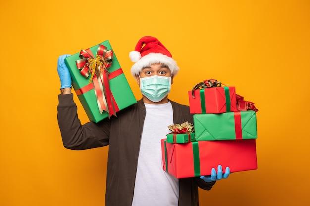 Экспедитор в рождественской форме держит подарочную коробку и носит маску и медицинские резиновые перчатки. Premium Фотографии