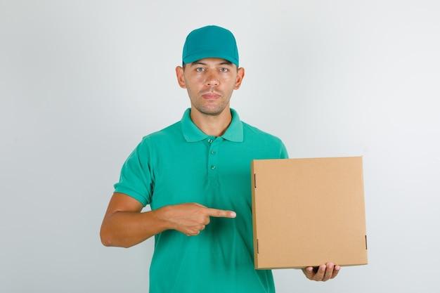 Доставщик в зеленой футболке и кепке показывает картонную коробку пальцем Бесплатные Фотографии