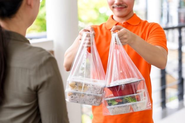 オレンジ色の制服を着た配達人がアジア料理を宅配ボックスで自宅の女性客に届ける Premium写真