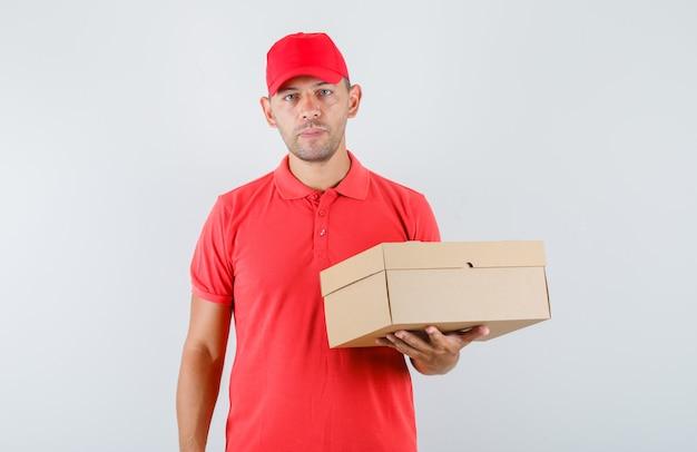 Курьер в красной кепке и футболке держит картонную коробку и выглядит уверенно Бесплатные Фотографии