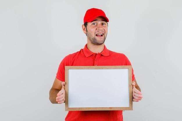 赤いtシャツ、ホワイトボードを保持し、陽気に見えるキャップの配達人 無料写真
