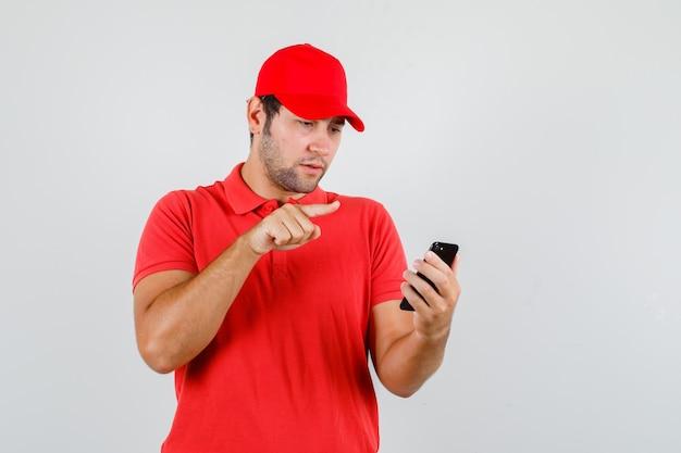 赤いtシャツ、指のサインでスマートフォンを見ているキャップの配達人 無料写真