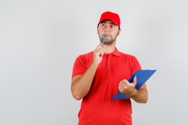 赤いtシャツ、クリップボードと鉛筆で見上げて物思いにふけるキャップの配達人 無料写真
