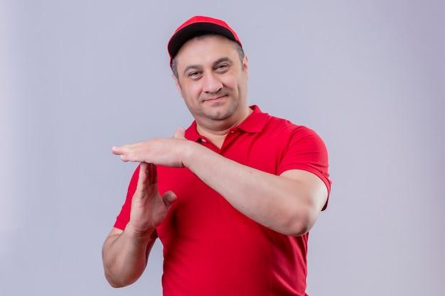 Доставщик в красной форме и кепке улыбается, делая жест тайм-аута на белом Бесплатные Фотографии