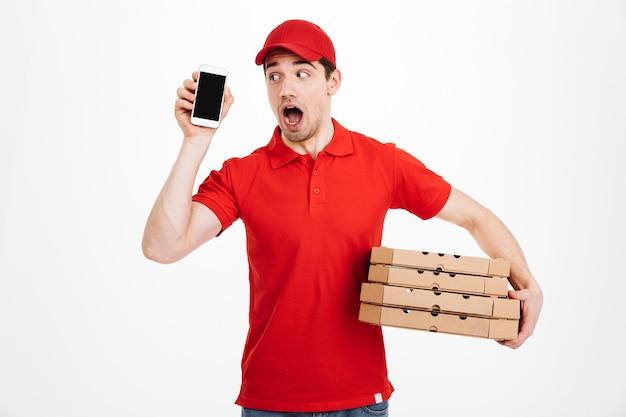 ピザの箱のスタックを保持しているセルを押しながら電話をしながら、白いスペースで分離された赤い制服を着た配達人 Premium写真