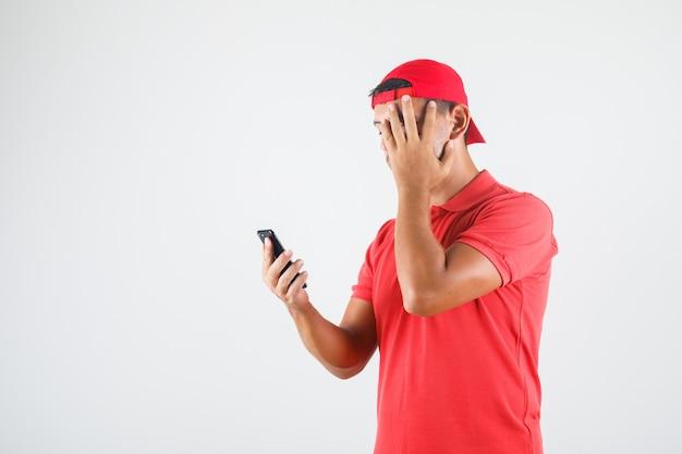 顔に手でスマートフォンを使用して慎重に見て赤い制服を着た配達人 無料写真