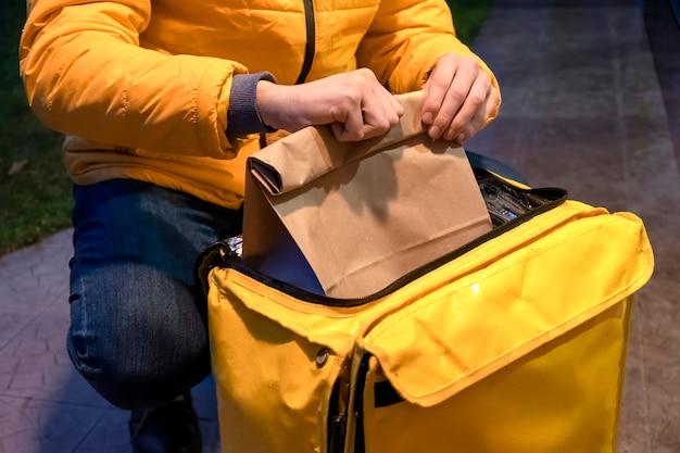 黄色いジャケットの配達人が黄色いバックパックを開けて、注文でバッグを取る 無料写真