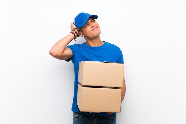 Delivery man over isolated white wall having doubts and with confuse face expression Premium Photo