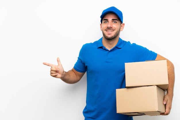 Delivery man over isolated white wall pointing finger to the side Premium Photo