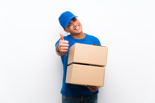 Delivery man over isolated white wall with thumbs up because something good has happened Premium Photo