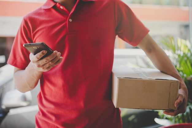 Delivery man looking customer address in mobile application. selective focus on hand. Premium Photo