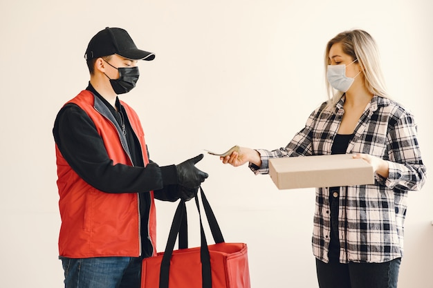 Delivery man in a medic mask with woman Free Photo