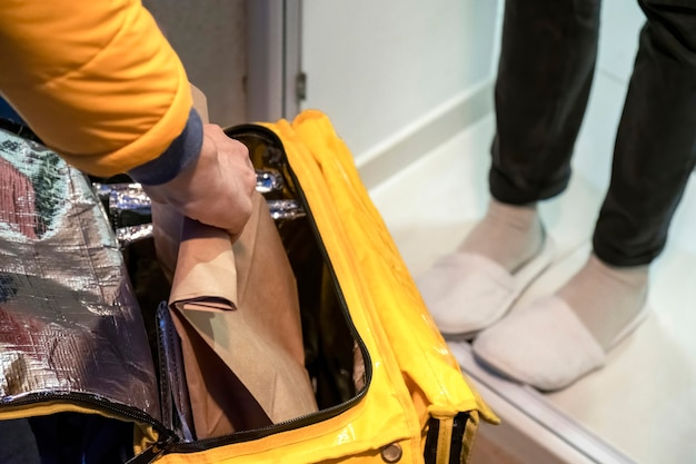 配達人が黄色いバックパックを開けて、注文のあるバッグを持って、他の人の足 無料写真