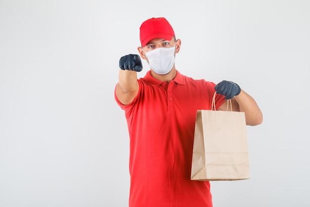 Доставщик, указывая пальцем на камеру с бумажным пакетом в красной форме, медицинской маске, перчатках Бесплатные Фотографии