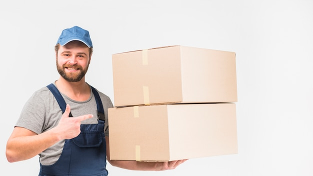 Delivery man pointing finger at boxes Free Photo