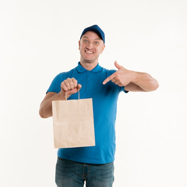 Delivery man pointing at paper bag Free Photo