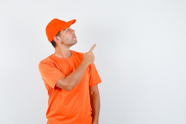 Fattorino rivolto verso l'alto mentre guarda verso l'alto in maglietta arancione e berretto e guardando concentrato Foto Gratuite