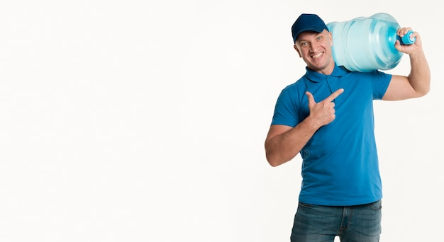 Delivery man pointing at water bottle on shoulder Free Photo