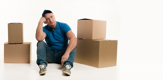 Delivery man posing with cardboard boxes Free Photo