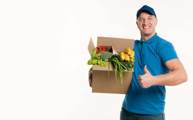 Delivery man posing with grocery box and thumbs up Free Photo