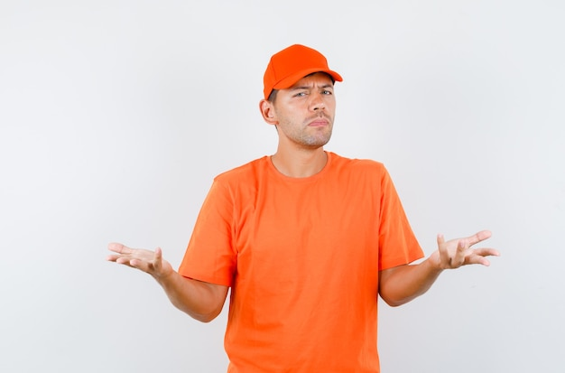 Delivery man raising hands in questioning manner in orange t-shirt and cap and looking confused Free Photo